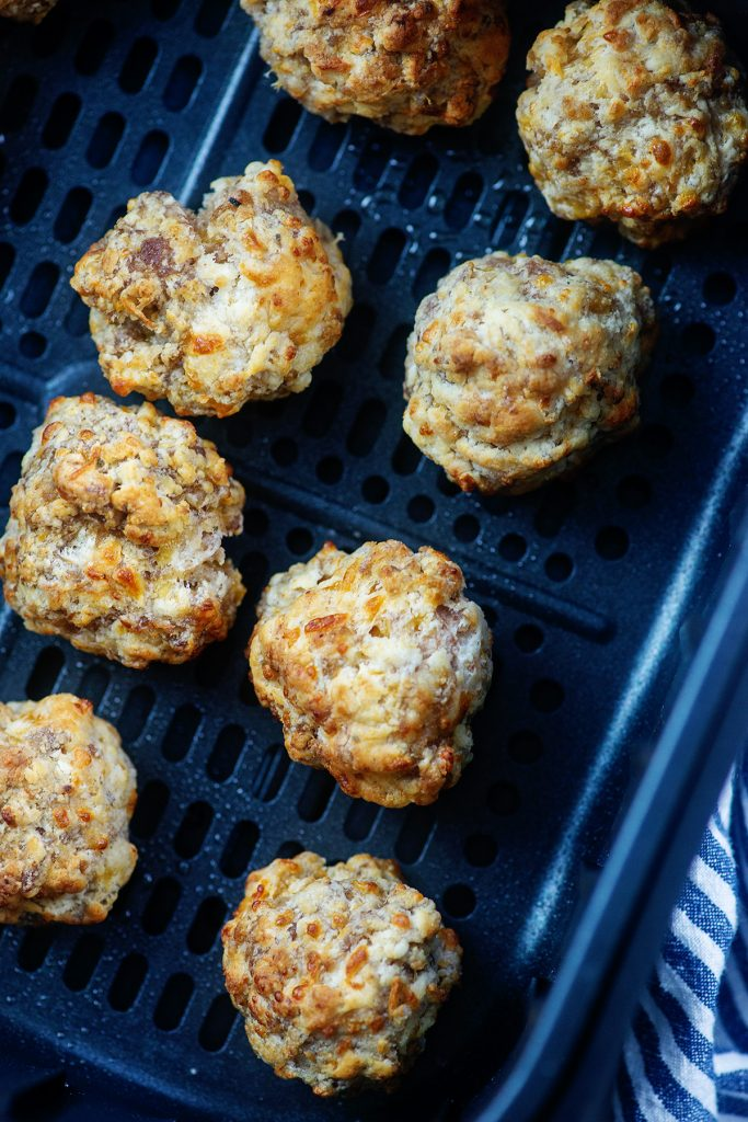 sausage balls lined up in an air fryer basket
