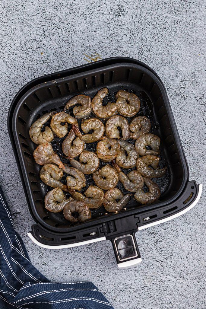 Glazed shrimp in an air fryer basket.