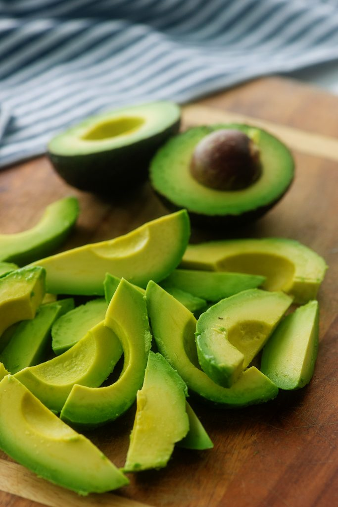Avocados cut into wedges on a cutting board.
