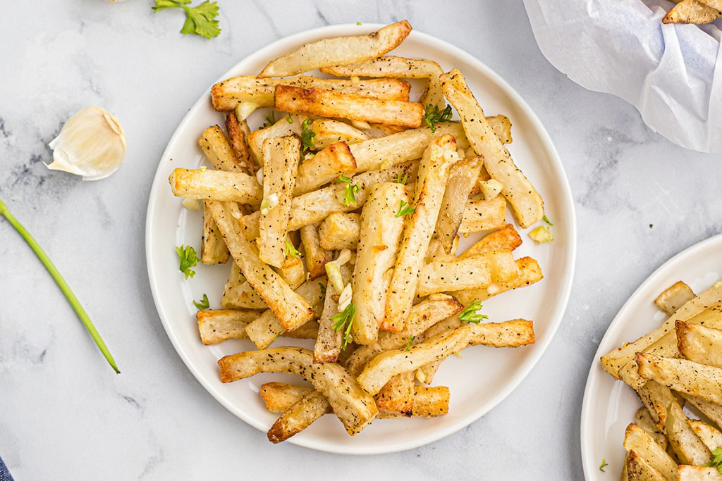 A close up of two plates of french fries side by side