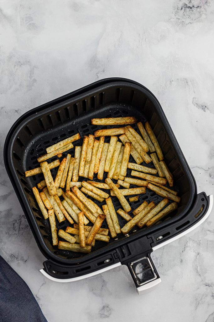 french fries spread out in an air fryer basket
