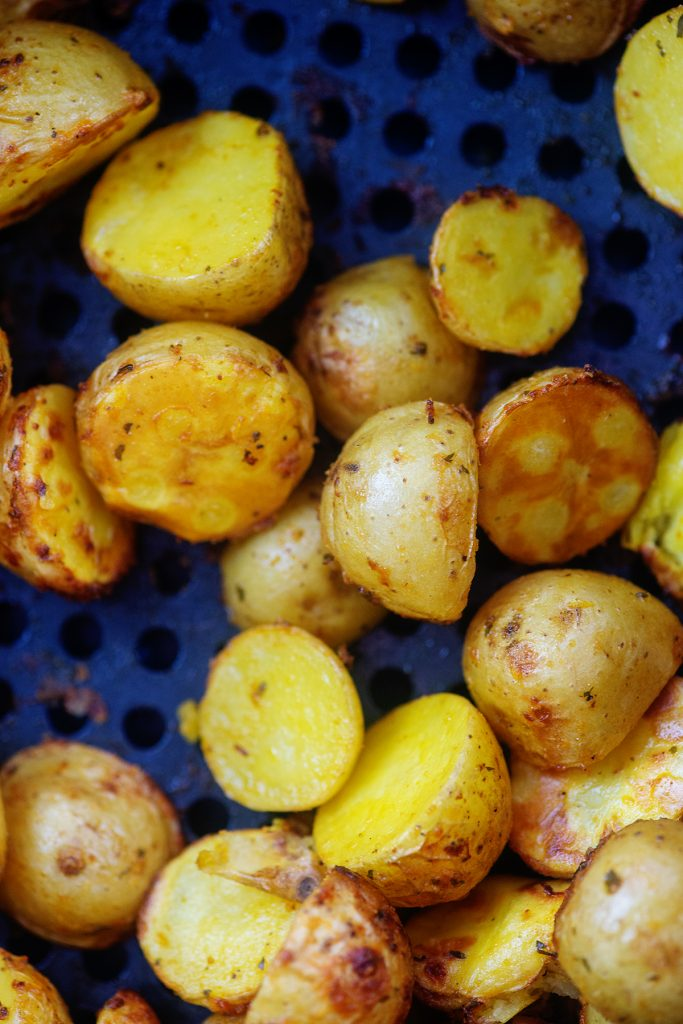 potato halves in an air fryer basket