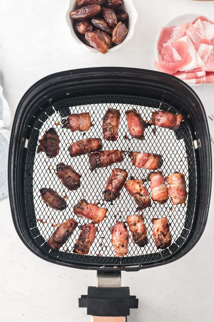 cooked bacon wrapped dates in an air fryer basket