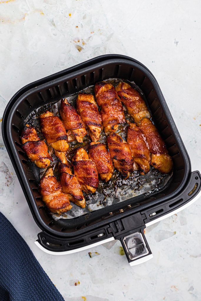 cooked bacon wrapped chickens in an air fryer basket