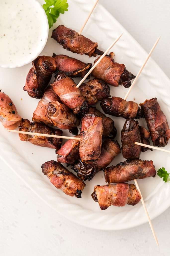 overhead view of bacon wrapped dates on a white serving tray