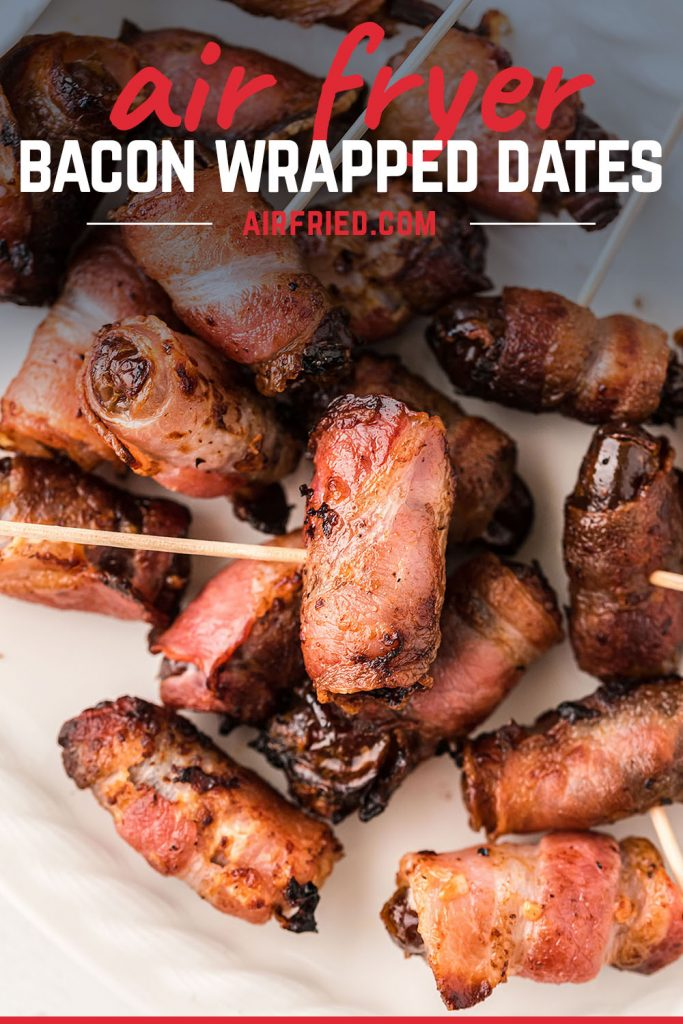 A close up of bacon wrapped dates on a white plate.