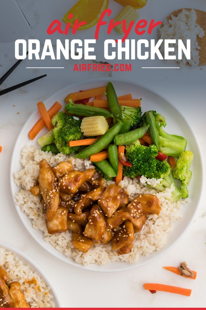 orange chicken on a small round plate next to orange slices