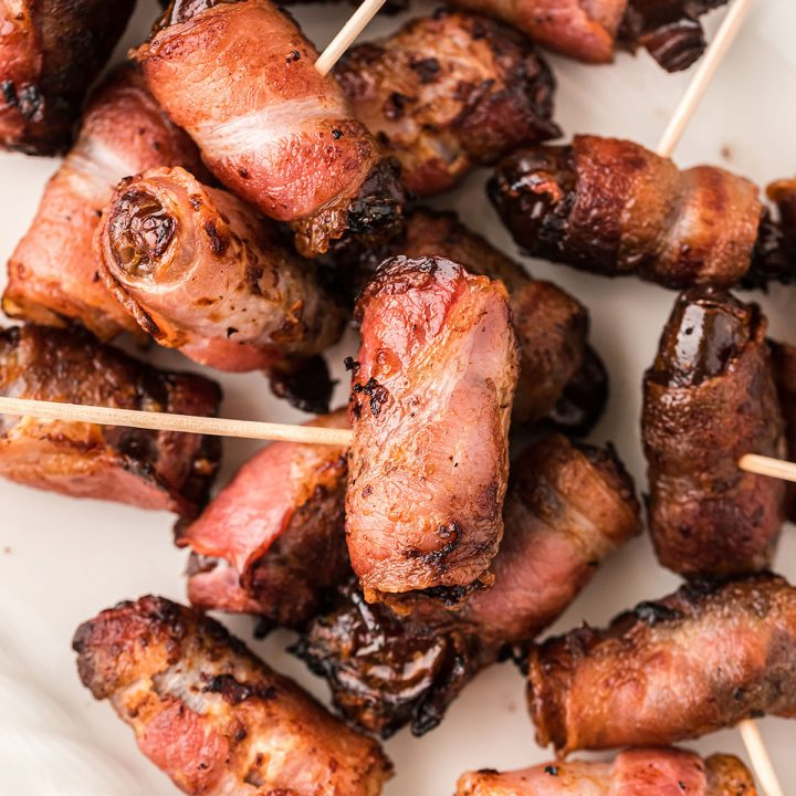 Close up of bacon wrapped dates with toothpicks in them.