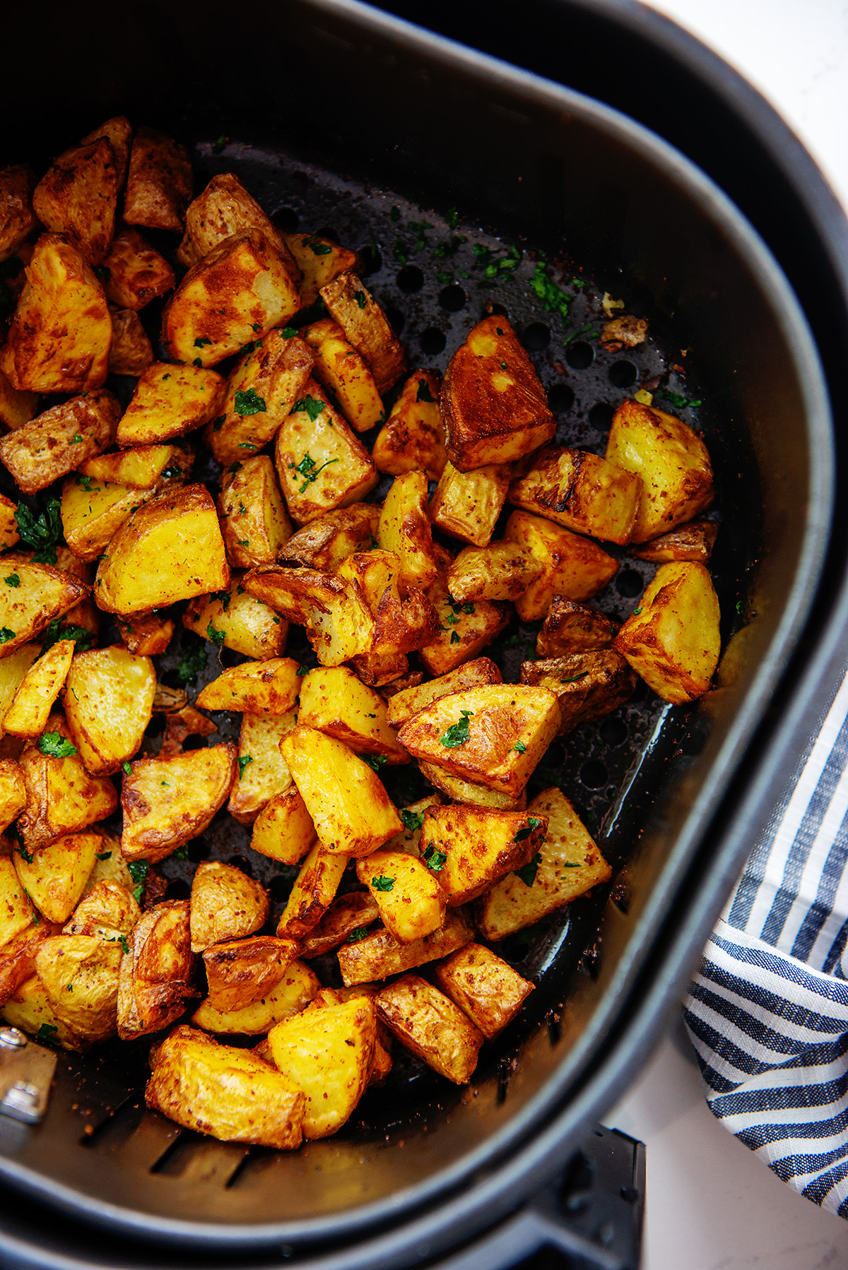 Overhead view of an air fryer basket full of roasted potatoes.