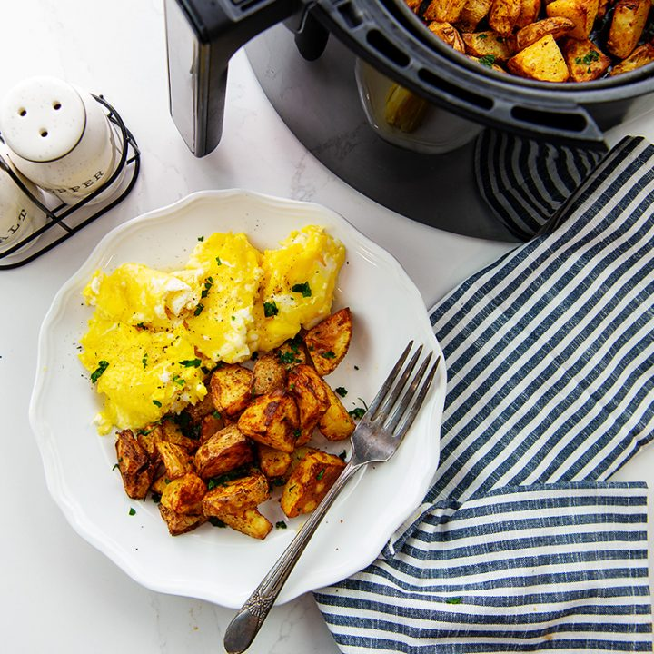 Overhead view of breakfast potatoes and eggs on a white plate next to an air fryer basket.