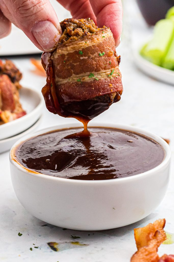 bacon wrapped bbq meatballs dipped in bbq sauce.