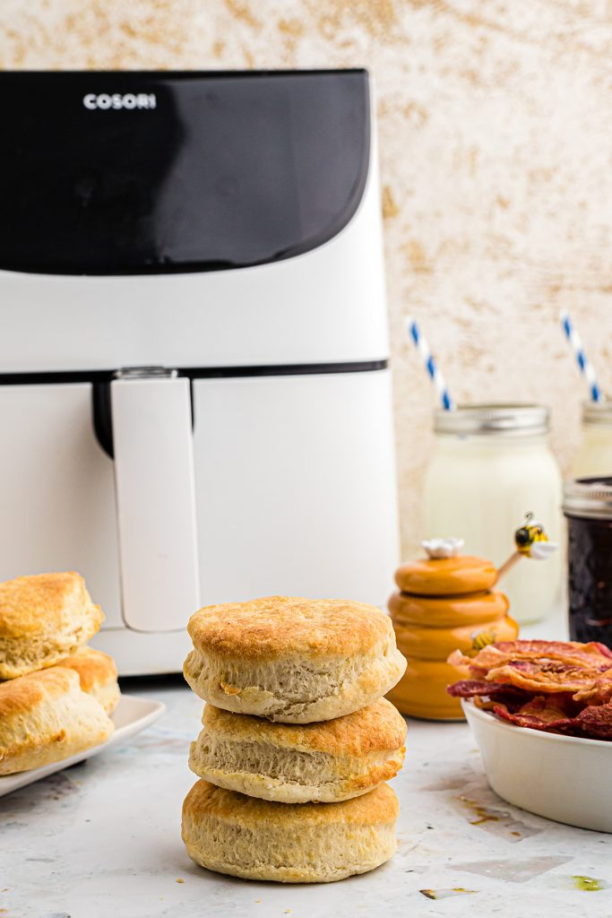 Biscuits stacked up in front of an air fryer.