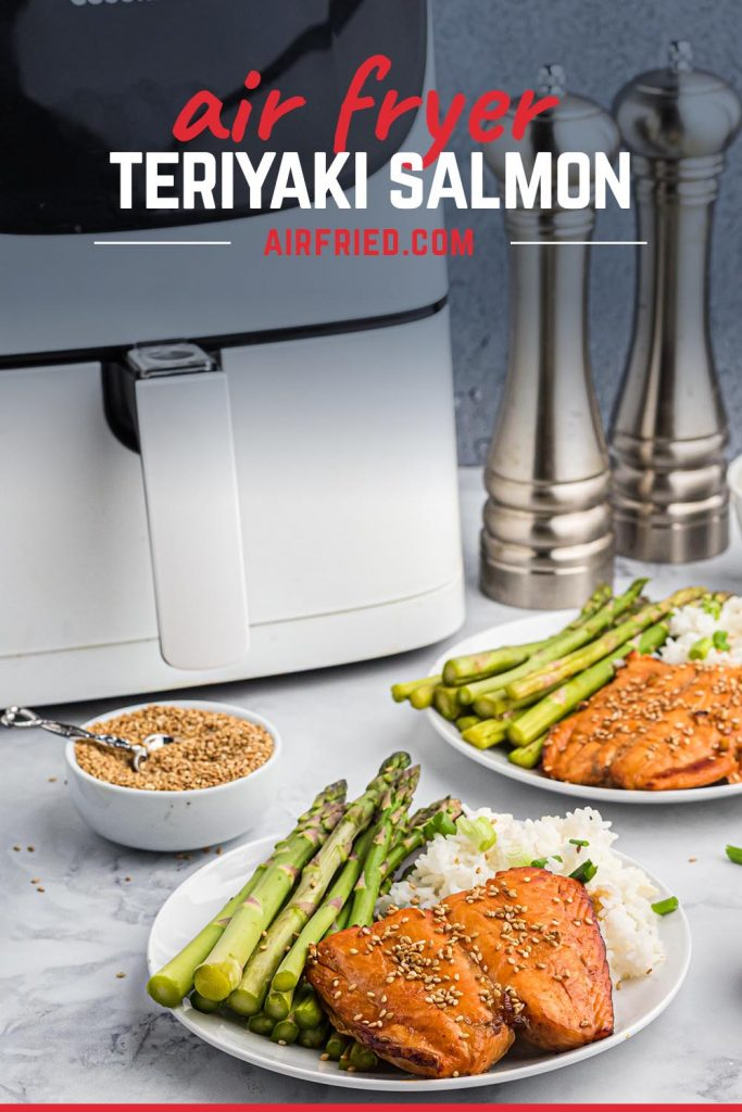 A dinner plate with salmon and asparagus in front of an air fryer.
