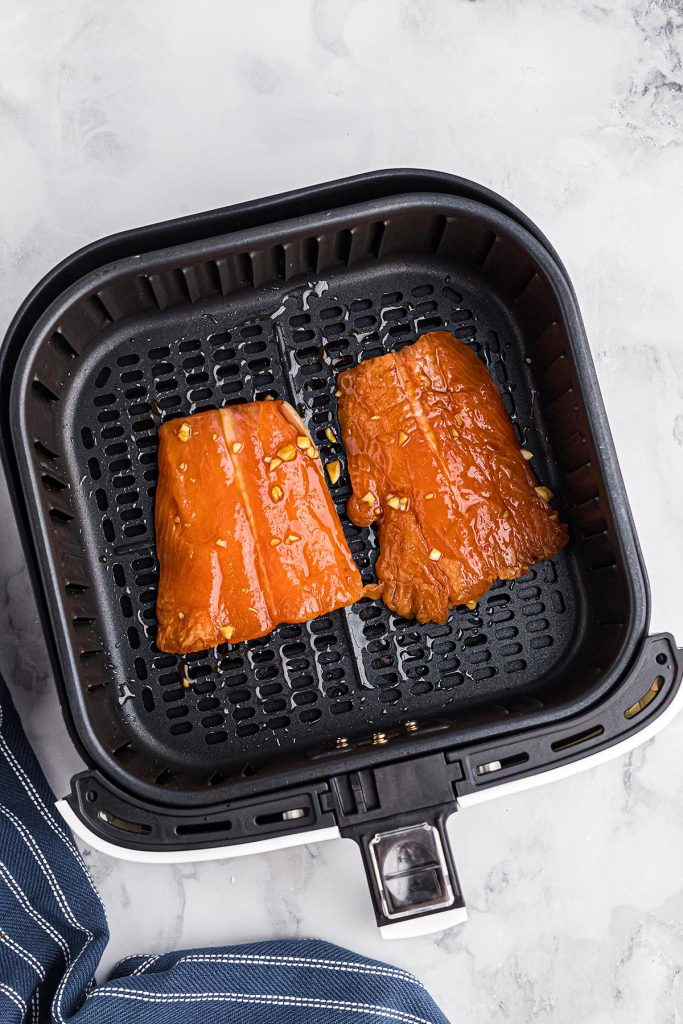 marinated salmon fillets in an air fryer basket