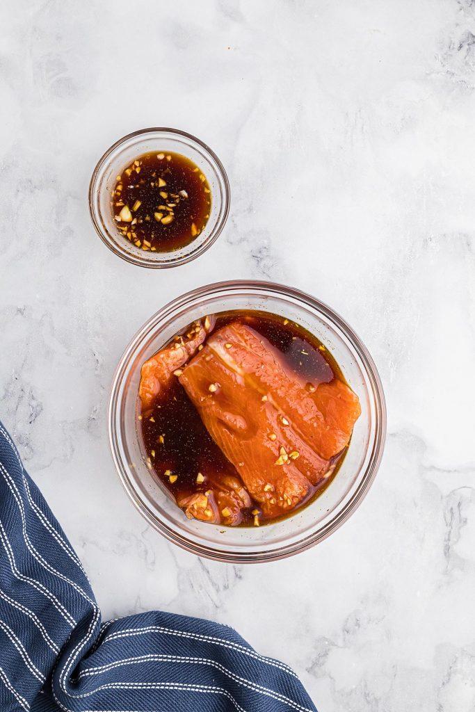 salmon being dipped into a teriyaki sauce
