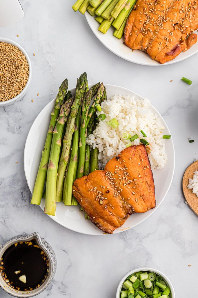 Overhead view of rice, salmon, and asparagus on a white plate.