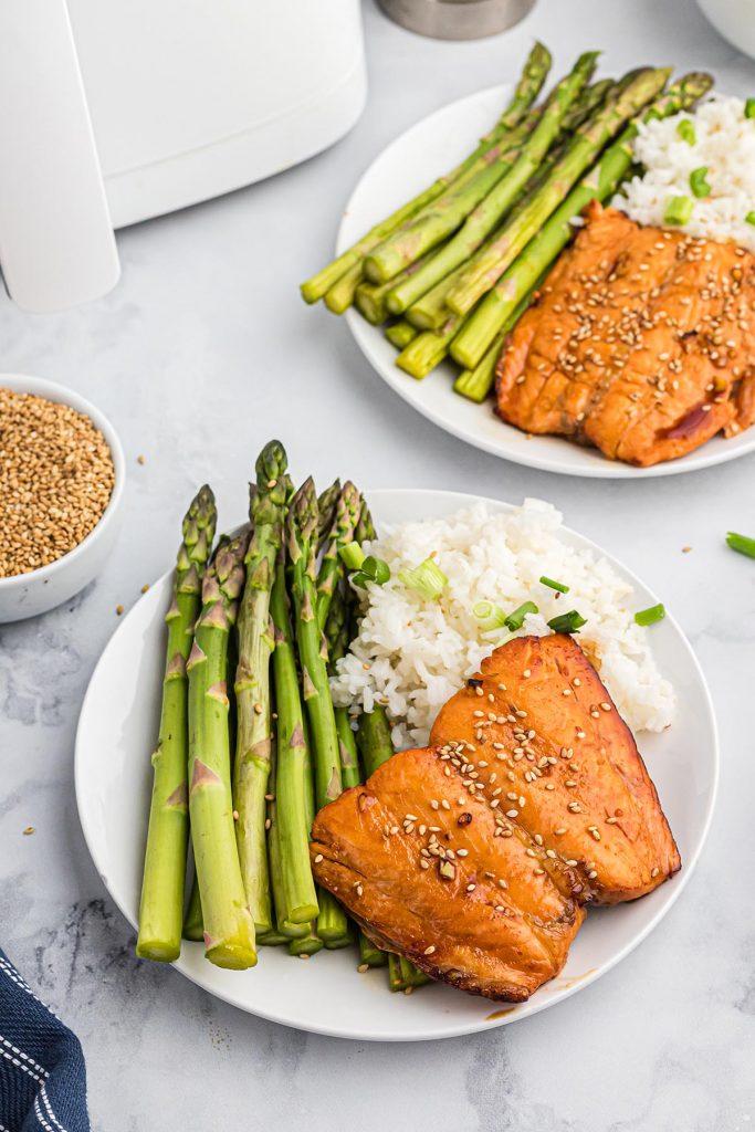 Two plates full of teriyaki salmon, asparagus, and rice