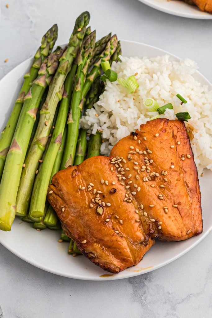 Asparagus, rice, and salmon on a small white plate.