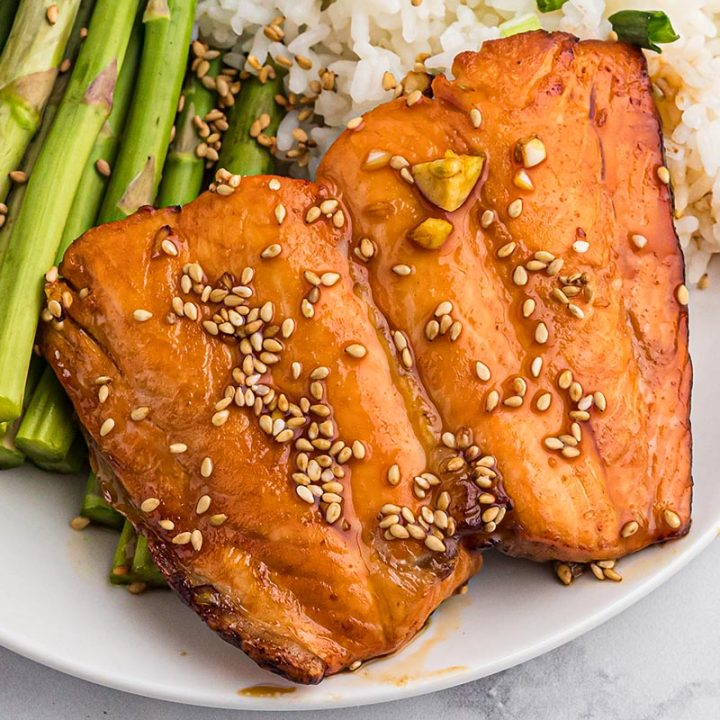 Close up of two pieces of teriyaki salmon on a white plate