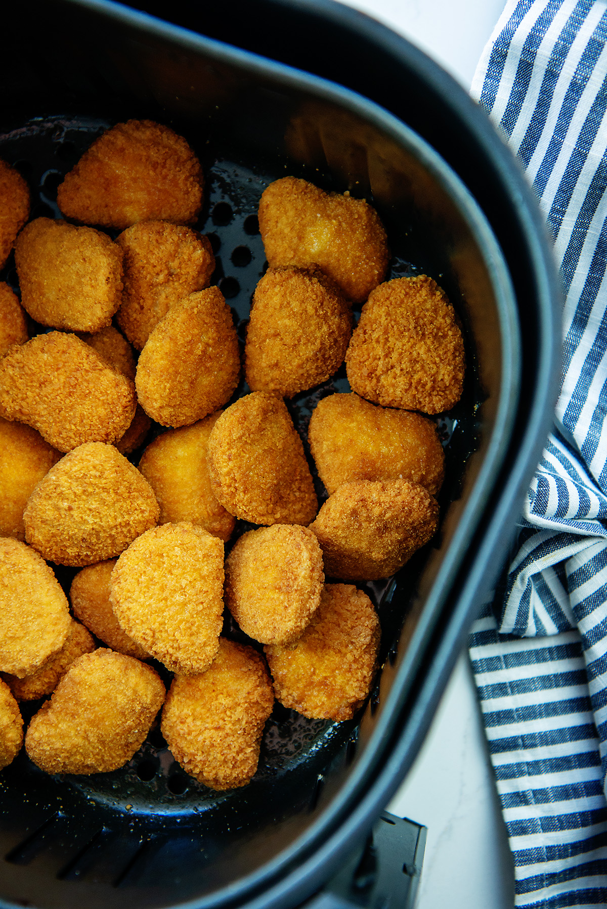 cooked chicken nuggets in an air fryer basket