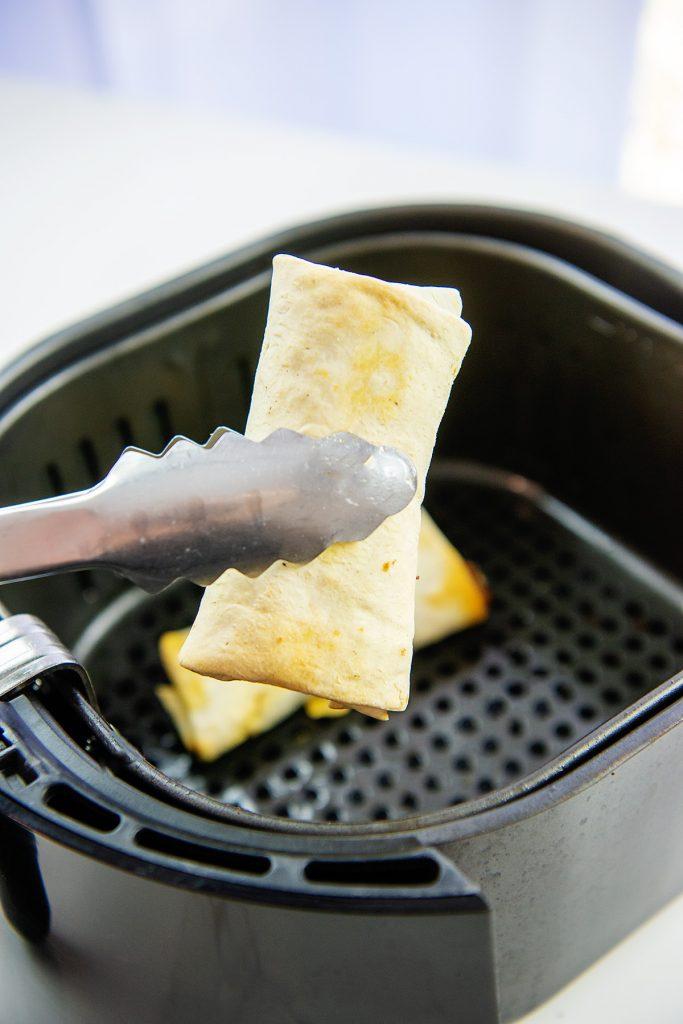 air fried burrito in tongs.