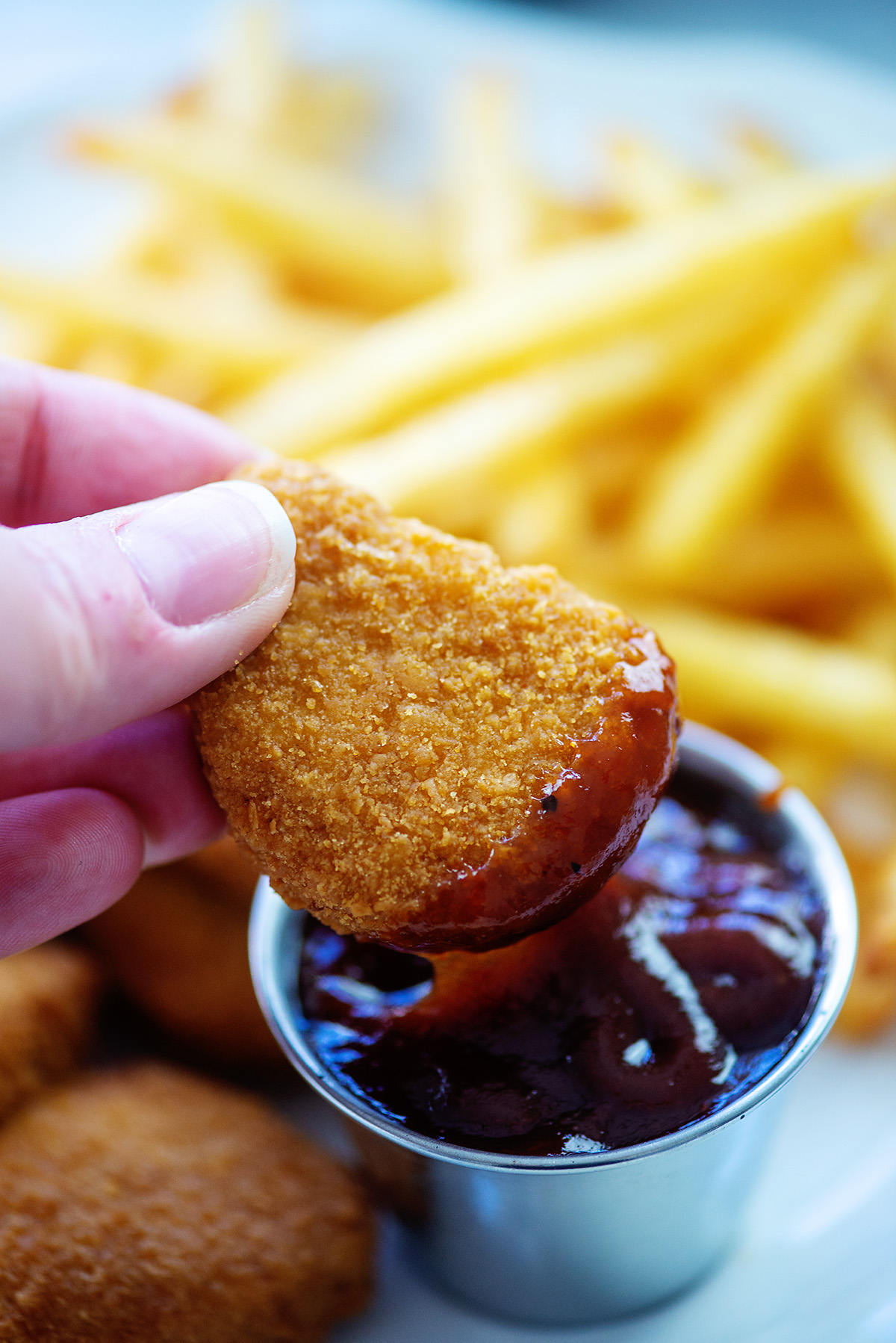 A close up of a woman dipping a chicken nugget in a bbq sauce