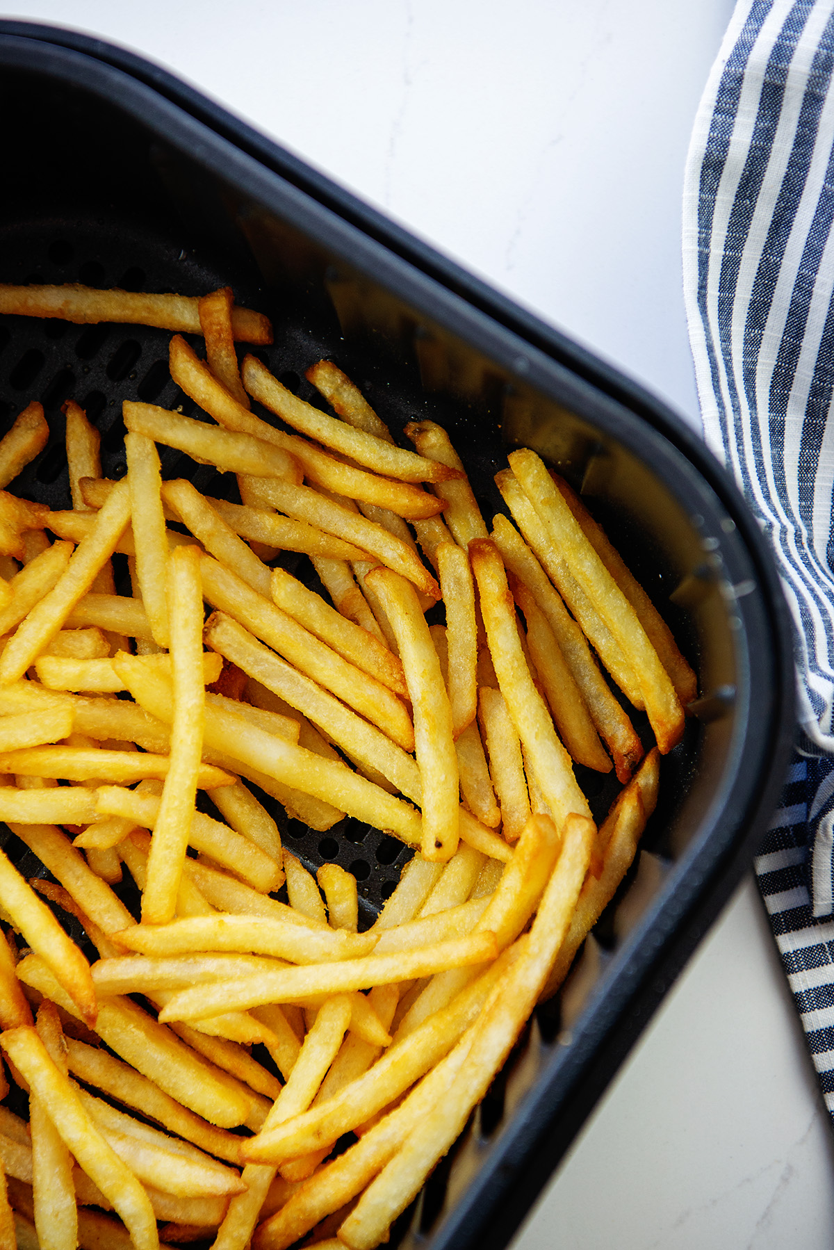 Air fryer basket full of cooked french fries