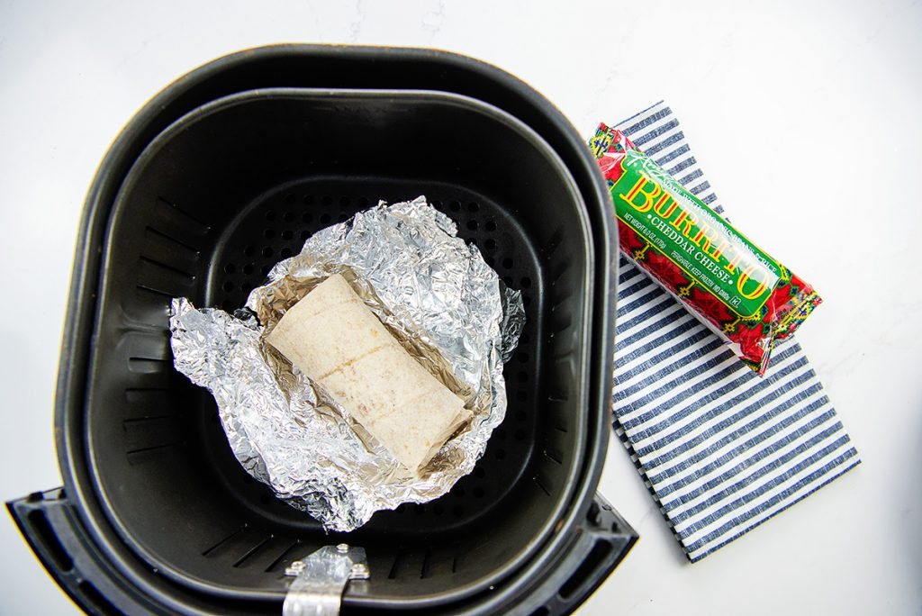 frozen burrito on a foil wrap in the air fryer.