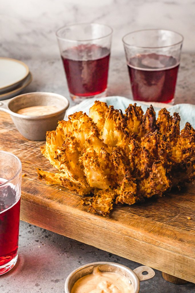 Blooming onion on a serving tray next to a cup of dipping sauce