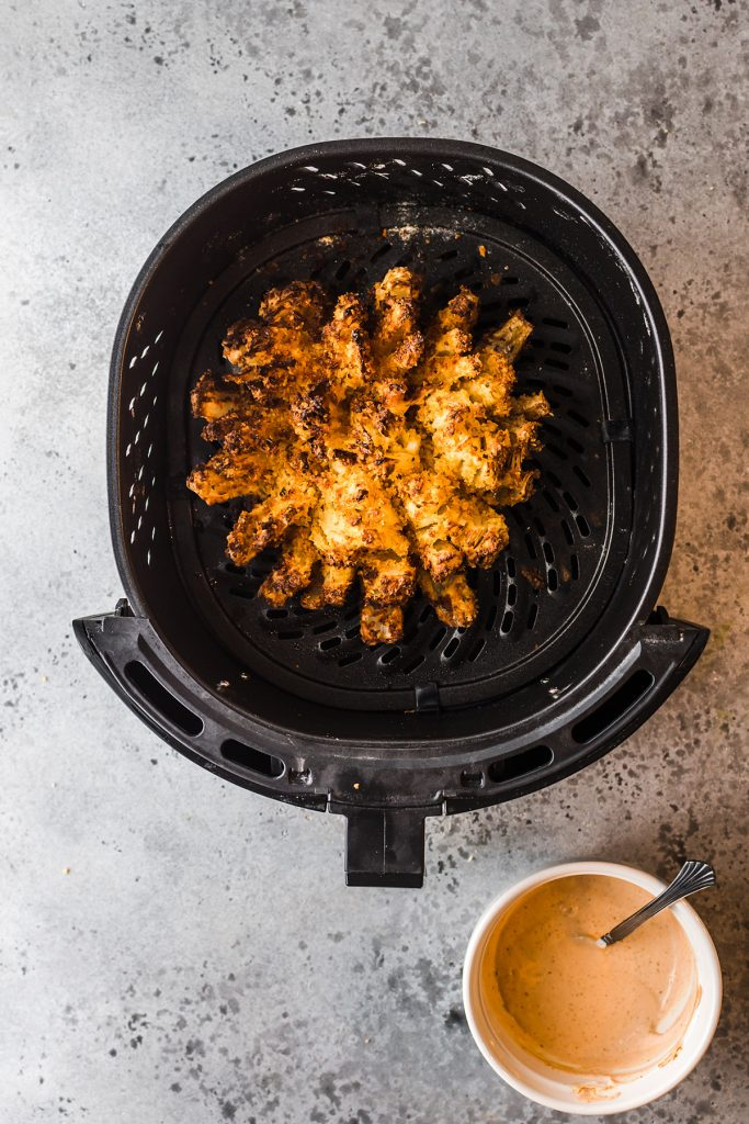 Overhead view of a blooming onion in an air fryer basket