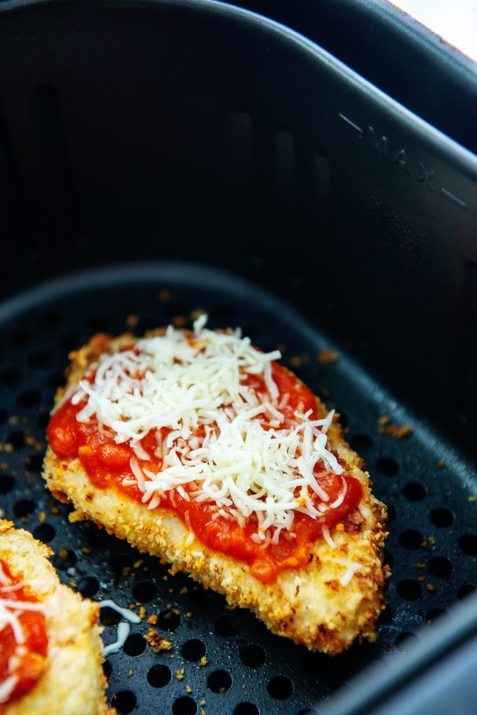 Cooked chicken parm with raw cheese on top in an air fryer basket