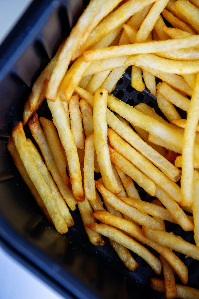 Closeup of cooked french fries stacked in an air fryer basket
