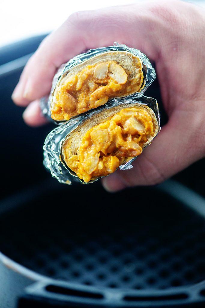 hand holding a frozen burrito over an air fryer basket.