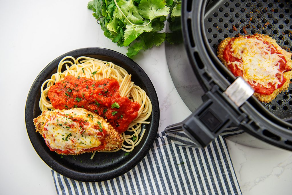 Overhead view of chicken parmesan next to an air fryer basket