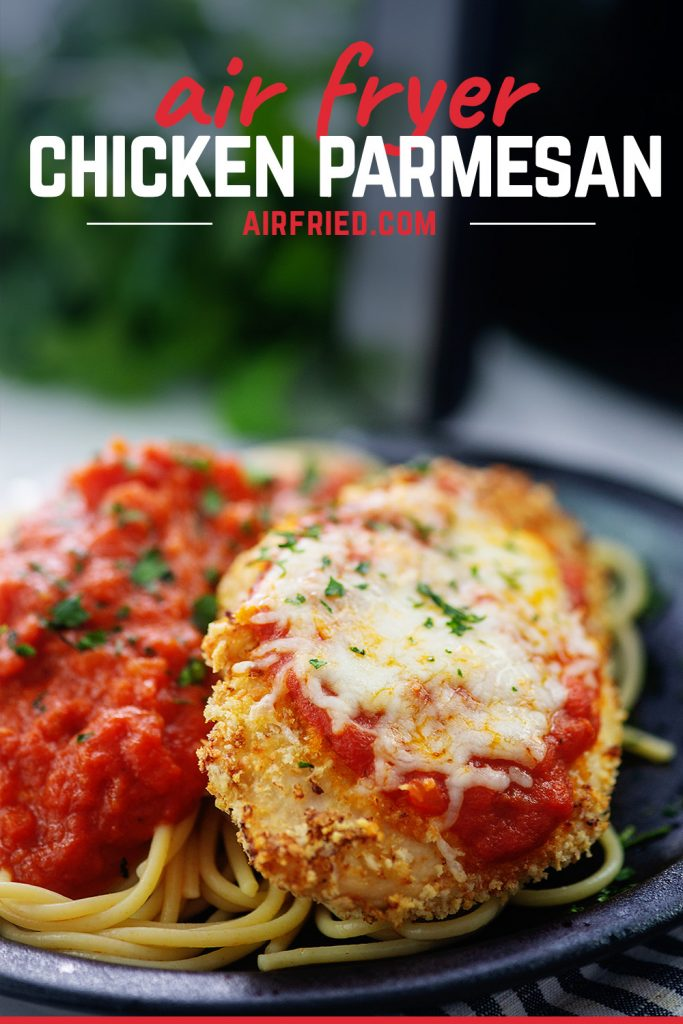 Chicken parmesan and spaghetti on a black plate