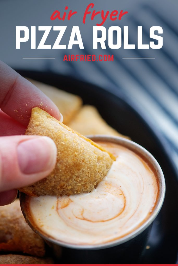 Close up of a woman dipping a pizza roll into a spicy ranch dip.