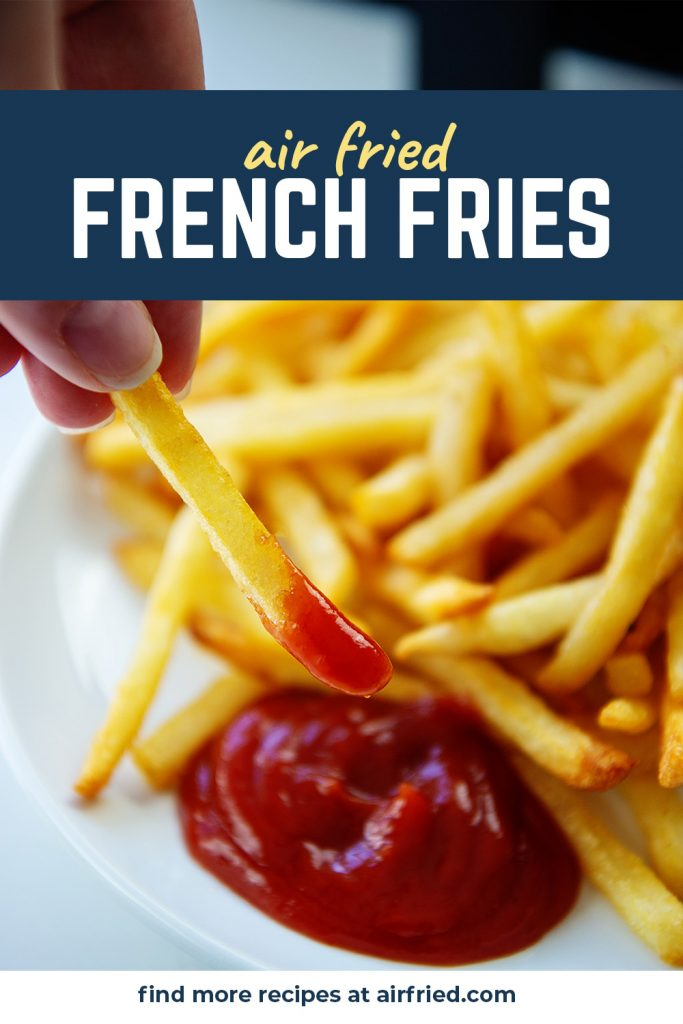 A person dipping a fry in ketchup