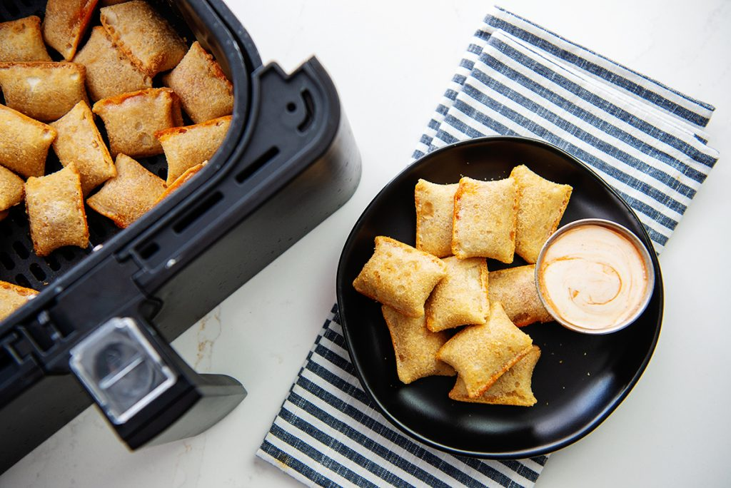 Pizza rolls on a black plate with a spicy ranch dip
