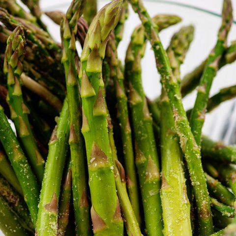 A closeup of seasoned asparagus in a glass bowl.