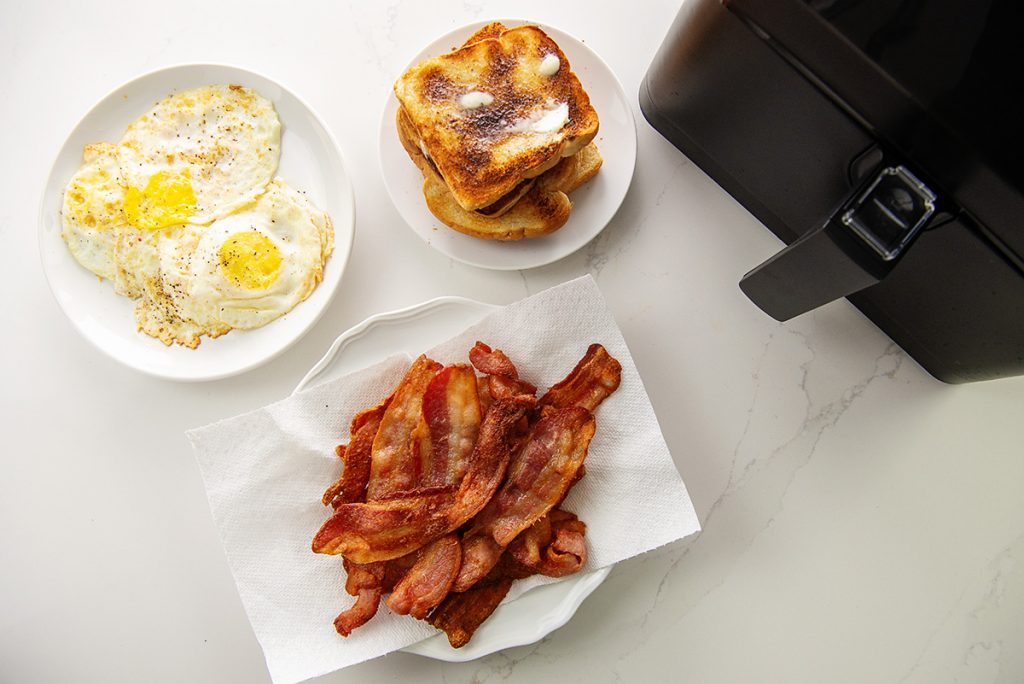 overhead view of bacon, eggs, and toast next to an air fryer.