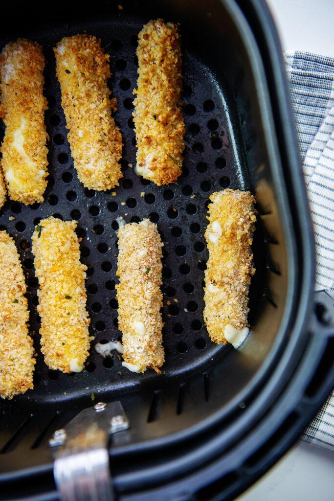 overhead view of mozzarella sticks in an air fryer basket