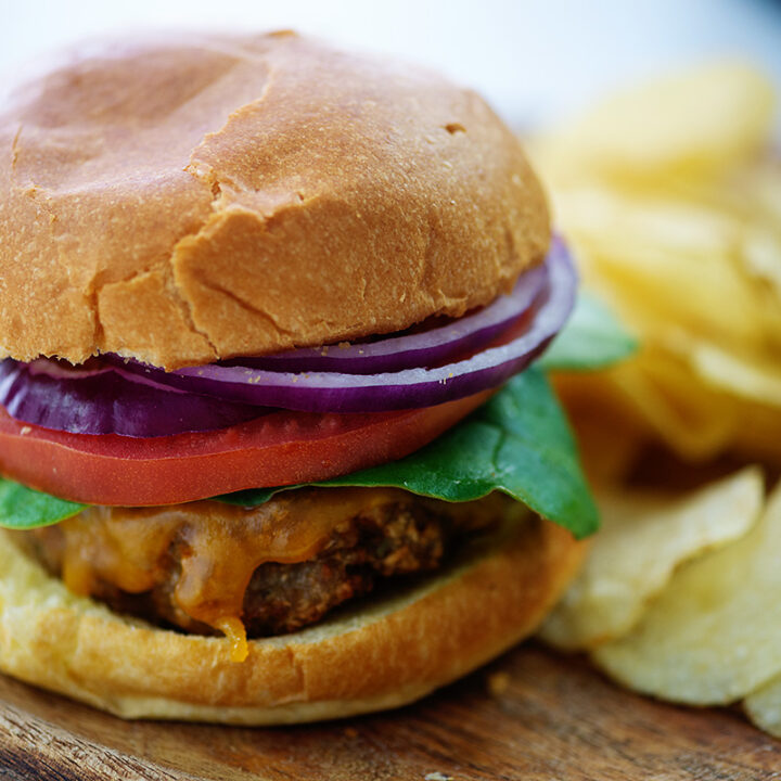Close up of a turkey burger with onion, tomato, and lettuce on it on a cutting board