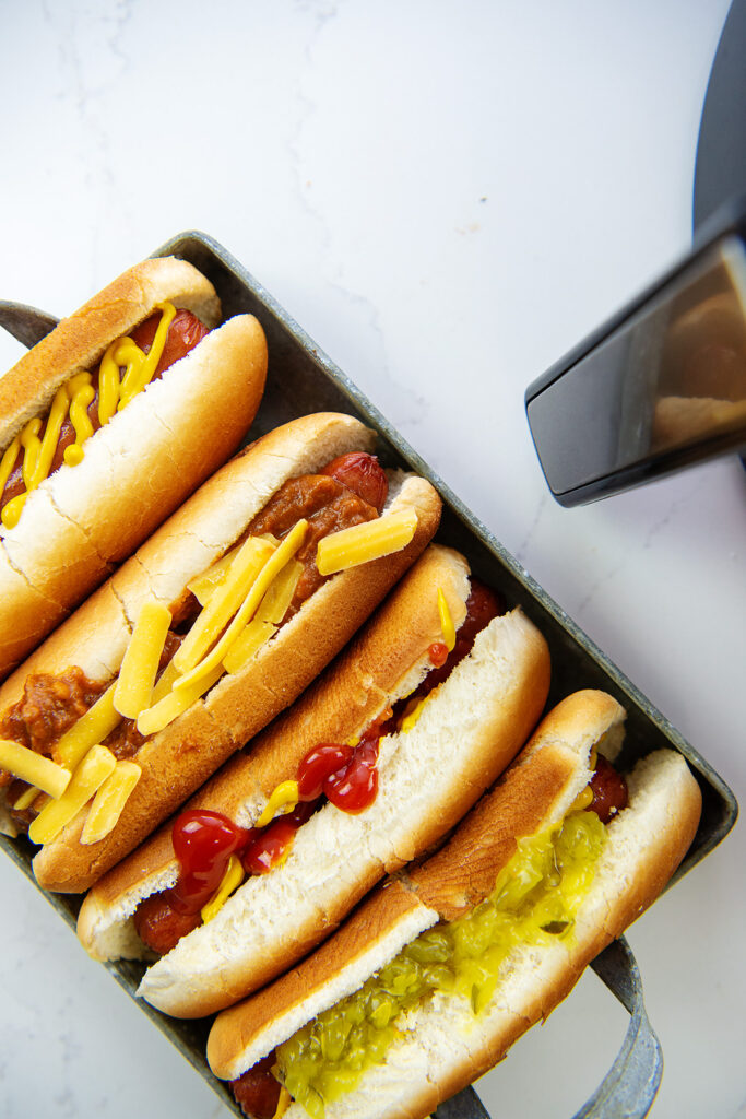 A close up of four hot dogs with various condiments on them in a serving tray