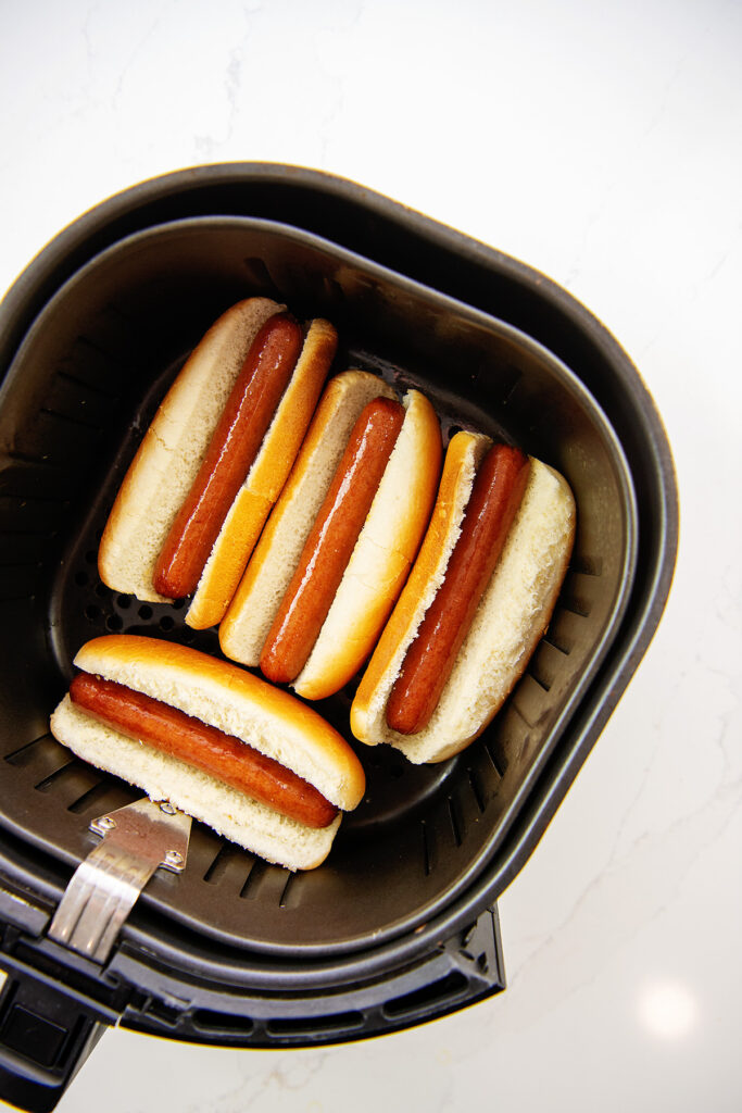 Overhead view of cooked hot dogs in an air fryer basket