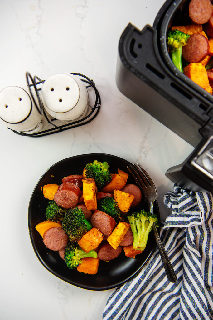Overhead view of a bowl of sausage and veggies next to an air fryer basket