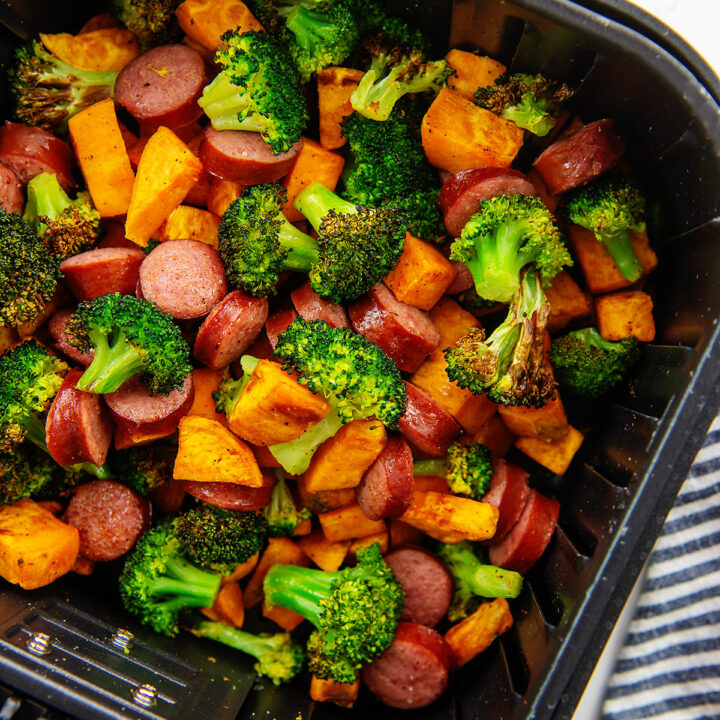 Overhead view of sausage and veggies in an air fryer basket after being cooked