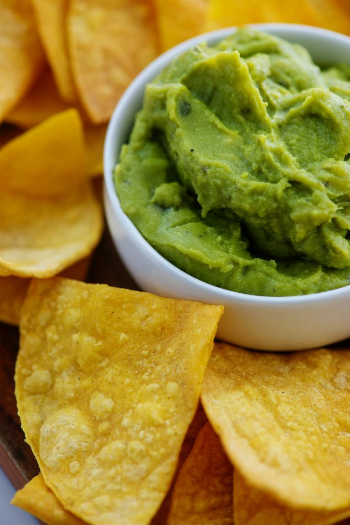 A cup of guacamole surrounded by tortilla chips