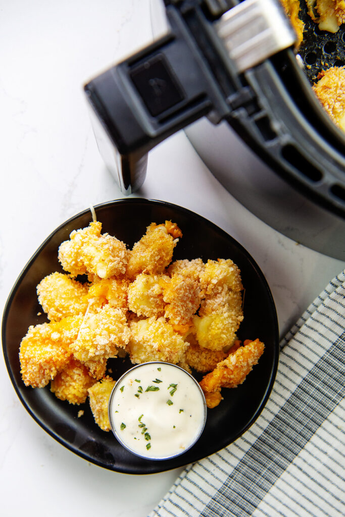 Overhead view of cheese curds and ranch dressing next to an air fryer basket