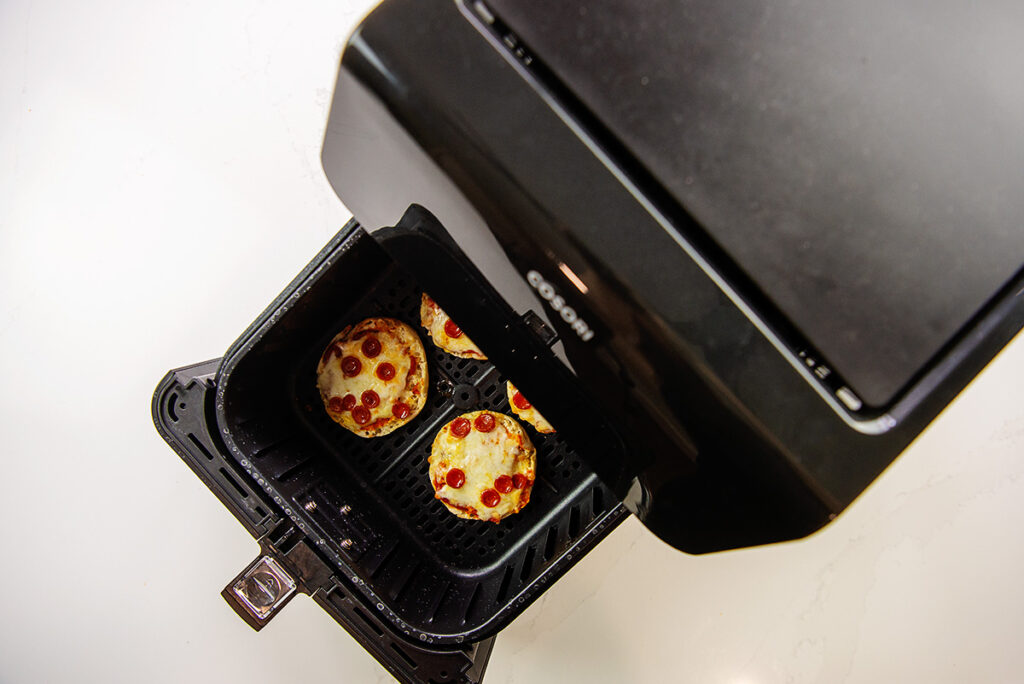 Overhead view of partially opened air fryer basket with cooked mini pizzas in it.
