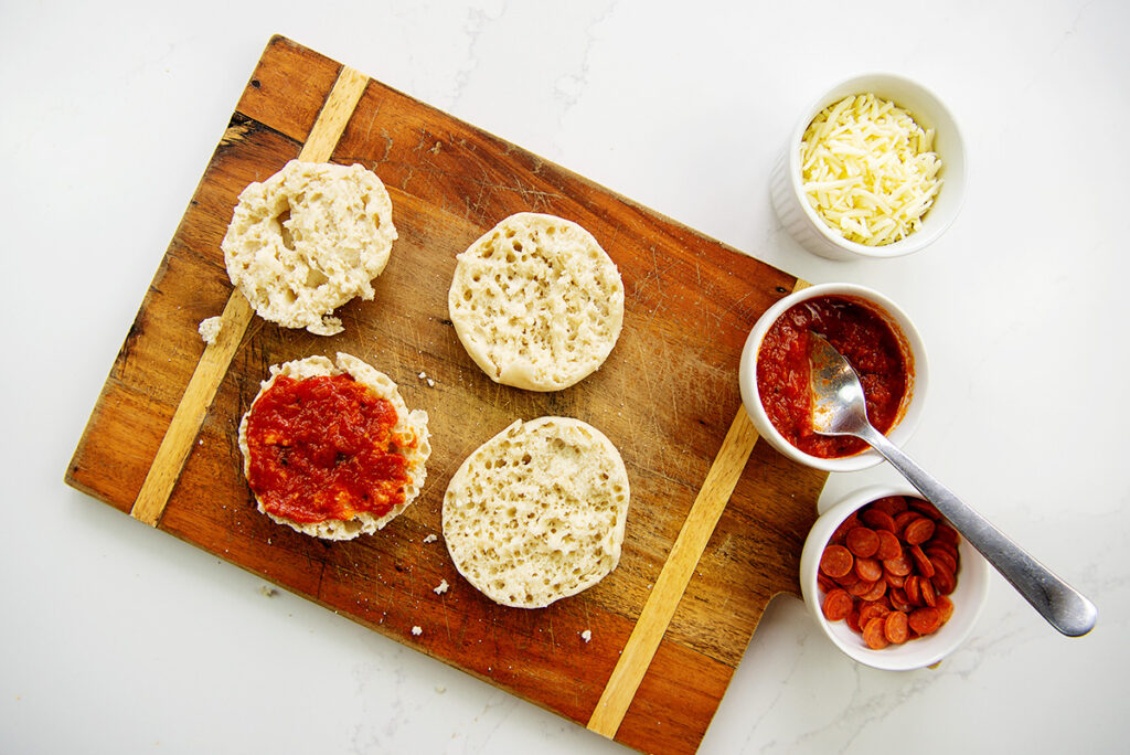 Overhead view of an English1 muffin on a cutting board next to cups of pizza toppings.